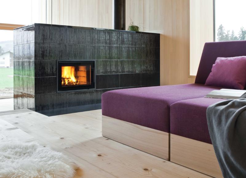 Moderner Kachelofen vor violettem Sofa